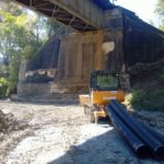 View below the bridge transporting diversion piping
